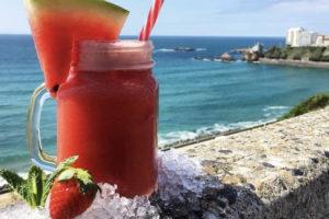 cocktail à la fraise posé sur le mur surplombant l'océan