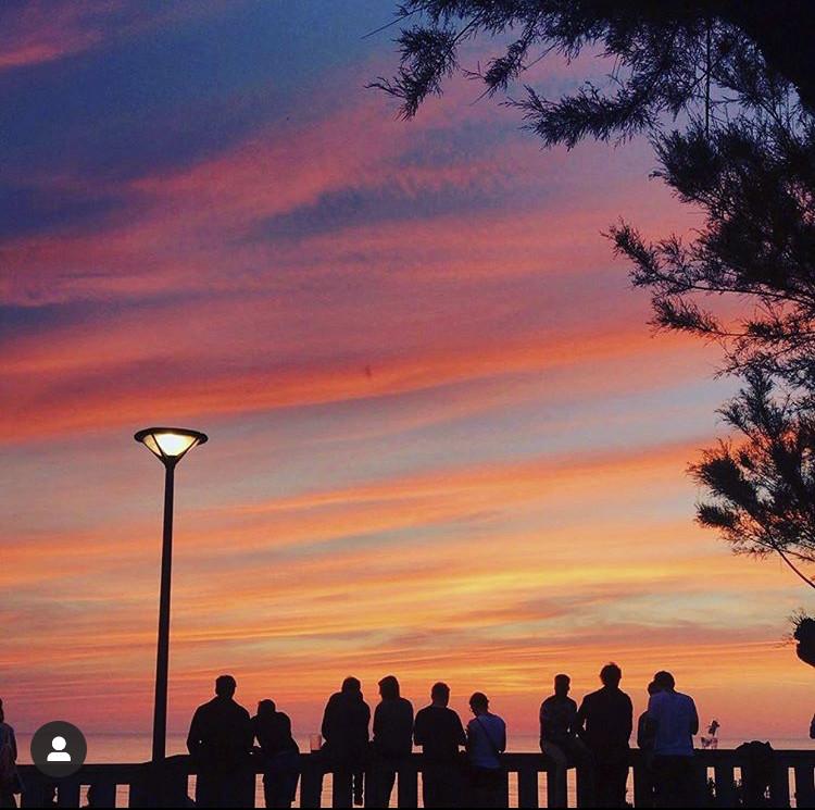 clients d'Etxola Bibi observant le coucher de soleil sur la Côte des Basques