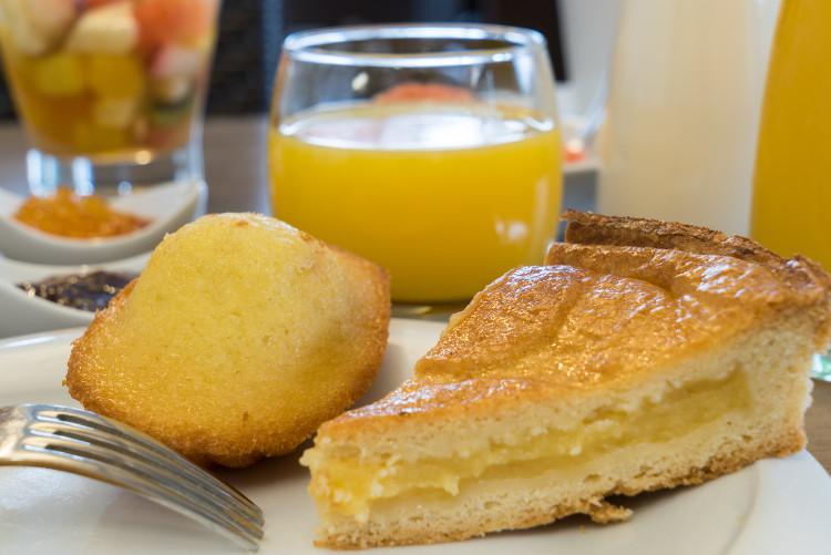 gâteau basque et madeleine devant un verre de jus d'orange servis au Sure Hotel Biarritz Aéroport