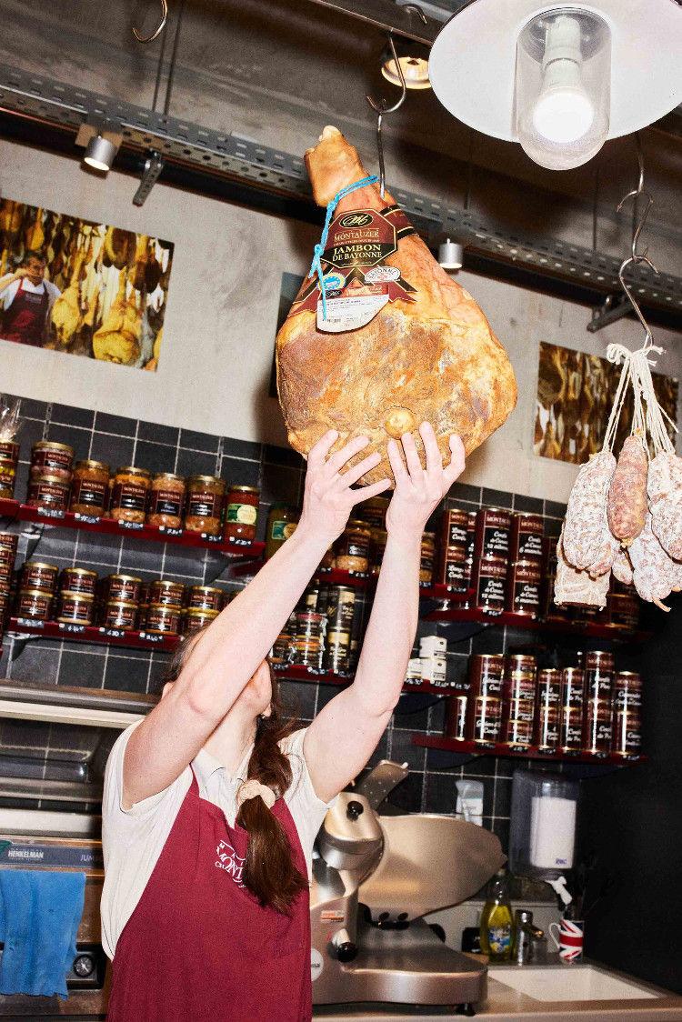 Homme de la maison Montauzer accrochant un jambon