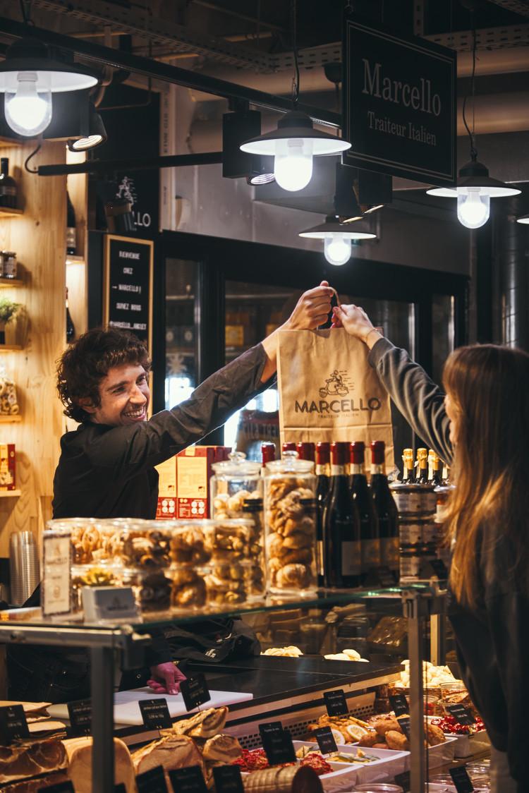 Homme donnant un sac à une cliente aux Halles des Cinq Cantons Biltoki