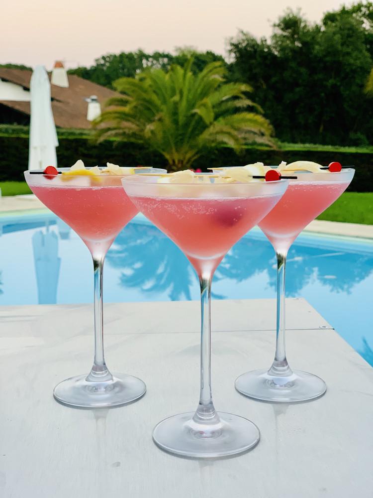 Verres à cocktail rose au bord de la piscine