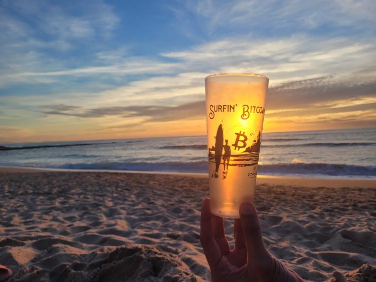 Verre Surfin' Bitcoin au coucher de soleil sur la plage