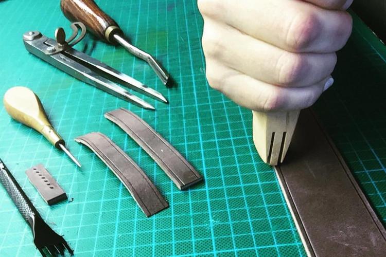 Main utilisant un outil pour travailler le cuir