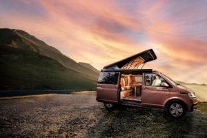 un van Woody Van devant un coucher de soleil en montagne