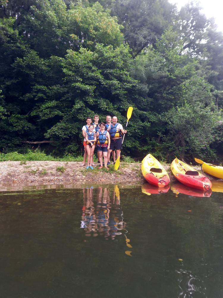 Famille sur la rive devant des canoë-kayaks