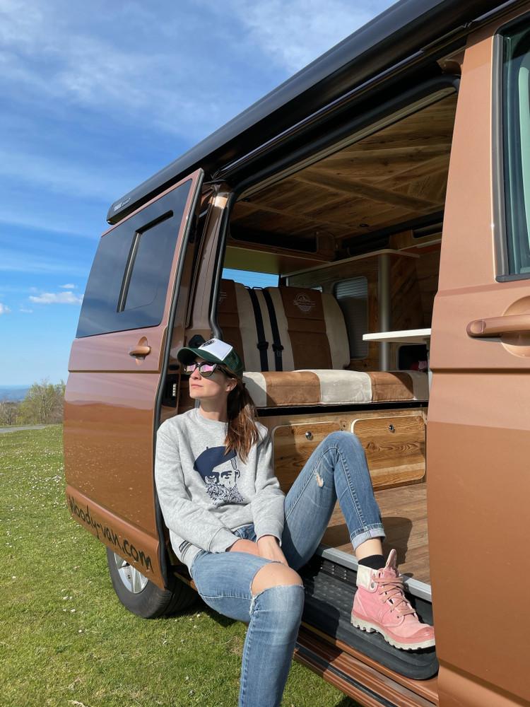 Femme prenant le soleil assise dans un véhicule aménagé Woody Van