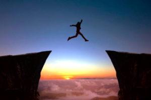 Personne sautant entre deux rochers au coucher du soleil